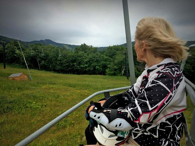 Mary taking the Snowshed Lift to mountain bike with Killington Peak in background