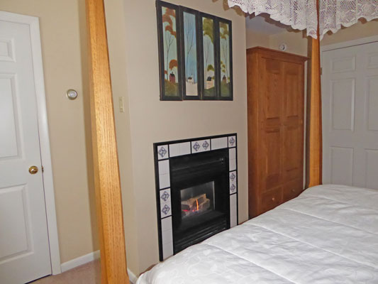 Fireplace at the foot of the canopy bed in Room 9